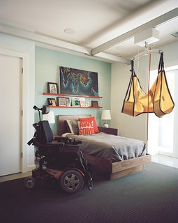 In Matthew's room, a Guldmann lift system joins a Hudson bed from Room & Board, while Atlas Industries bookshelves showcase personal treasures. Carpet by Bloomsburg, backed with rubber padding so the wheelchair doesn't sink, is inlaid to prevent trip hazards.