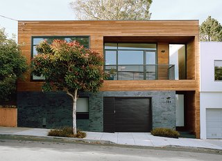 The contemporary renovation of this 1930s fixer upper resulted in a 1,800-square-foot residence that feels expansive, thanks to an ingenious use of natural materials and space-saving design. For the facade, architect Cary Bernstein used Ironspot clay tiles and FSC-certified cedar. The entryway was also reconfigured for the street level.  Guests then ascend straight to the main living space.