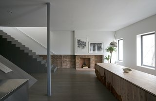 Architect Alex Gil and his wife, Claudia DeSimio, affixed a 750-square-foot addition to the roof of a 19th-century Williamsburg townhouse, transforming their cramped third-floor apartment into a modern duplex. The original fireplace remains, but has been stripped down to exposed brick, as have the surrounding walls, creating an almost wainscot-like design of exposed brick with flat white drywall above.
