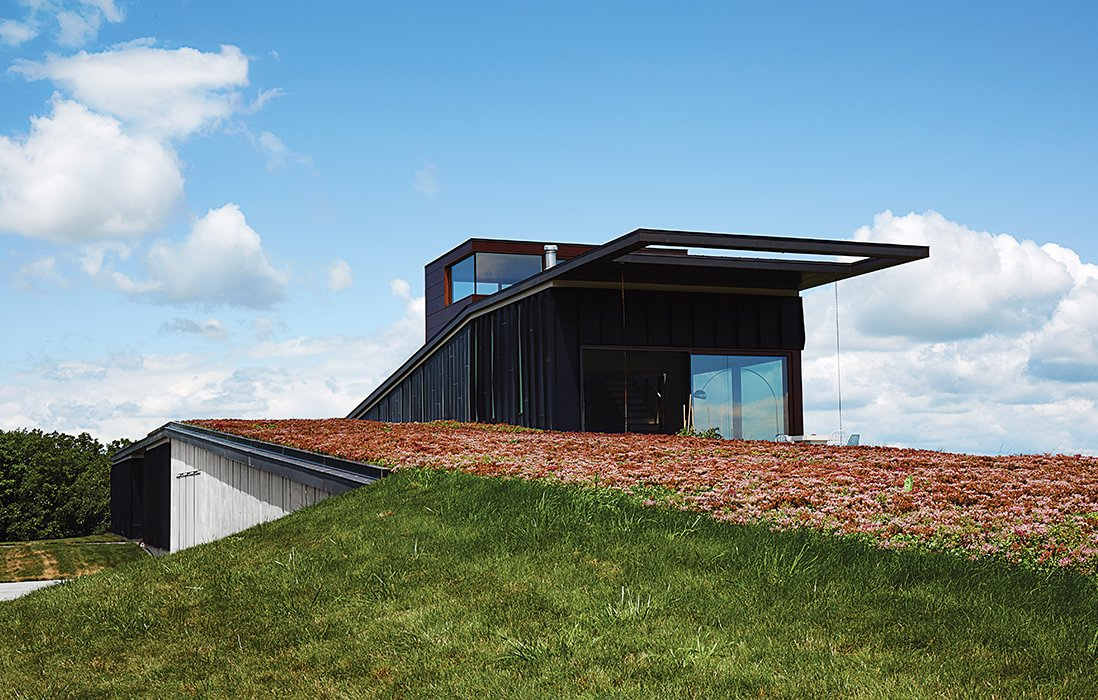 "House Building Type, Outdoor, Wood Siding Material, and Grass The house that architects Brian Johnsen and Sebastian Schmaling designed for Chele Isaac and John Neis appears to pop up from Wisconsin's ""driftless area,"" an effect that is enhanced by a sedum roof that changes color with the seasons.  Photo 1 of 10 in A Prairie Escape Embraces the Landscape with a Green Roof"