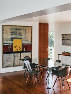 In the dining room, artworks by Alan Davie (at left) and Martin Bradley join a Norman Foster dining table.