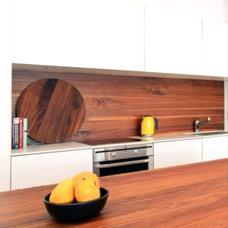 This sleek wood  kitchen counter has a matching wood backsplash designed by Christian Woo.