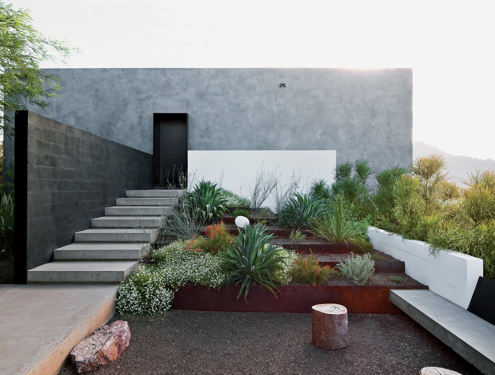 Outdoor, Hardscapes, Desert, Raised Planters, and Small Patio, Porch, Deck Burnette sought to maintain the property's natural vegetation and rocky ground surface.  Photo 6 of 8 in This House Doesn't Hold Back and Embraces the Desert
