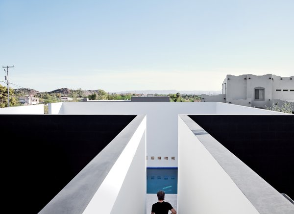 "The pool is sheltered on all sides by white plaster walls, a space envisioned by the architect as a volume that's ""half terrace, half cool-water retreat...projected toward the canopy of the desert sky."""