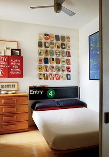 Book jackets by Alvin Lustig and a vintage subway sign hang over a custom bed by Jeff Jenkins Design + Development.