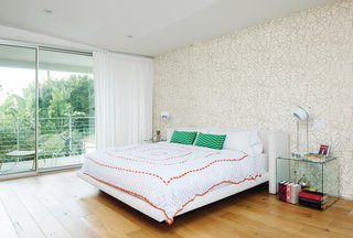The master bedroom features wallpaper by Erika Wakerly. The glass tables next to the Croft House bed were gifts.