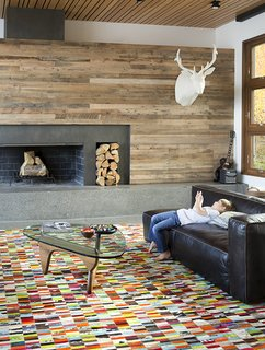A Custom, LED-Lit Slide Twists Through This Family-Friendly Vacation Home - Photo 3 of 11 - When building their dream retreat in Jackson Hole, Wyoming, Steve and Alexi Conine worked with architect Brad Hoyt to create a smart house that fused technology and design. Like the rest of the home, the living-room furnishings blend high design, comfort, and kid-friendliness, including a table by Isamu Noguchi for Herman Miller, a leather sectional sofa from Four Hands, a cashmere cableknit-covered elk mount by Rachel Denny, and a custom, multicolored cowhide patchwork rug by Linie Design.