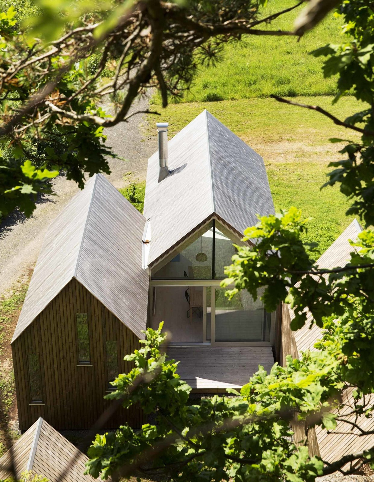 Exterior, Gable RoofLine, and House Building Type A rear deck is nestled behind the central cabin, flanked by the sleeping quarters. Inside, the dining table sits beneath a single hanging lamp.  Photo 4 of 6 in This Cozy Retreat Holds the Cure for Cabin Fever