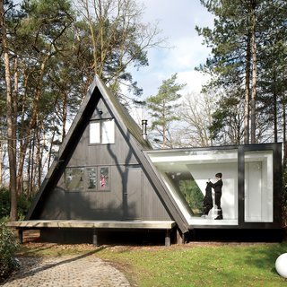 For this tiny house in the Belgian forest, a little extra square footage comes in the form of a glassed-in addition with a stellar view.