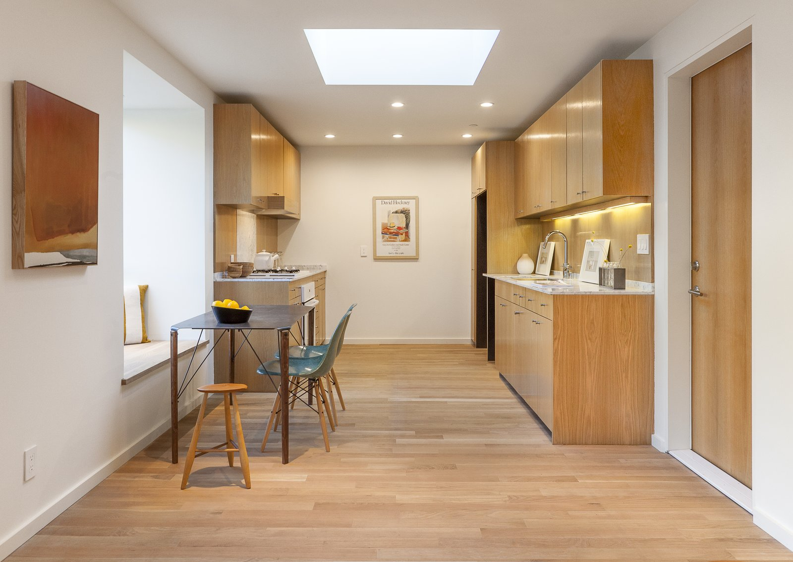"""White oak was also used for the kitchen cabinetry, and white marble for the countertops. In the open-plan dining area, another window seat pulls double duty as a bench for the kitchen table.  """"The bump-outs are designed to function as built-in furniture,"""" he says. """"I loved the idea of turning the walls into miniature habitable spaces, and making the house itself part of the furniture.""""  Photo 8 of 9 in Twin Houses on Tiny Lots Stretch Outward for Space"""