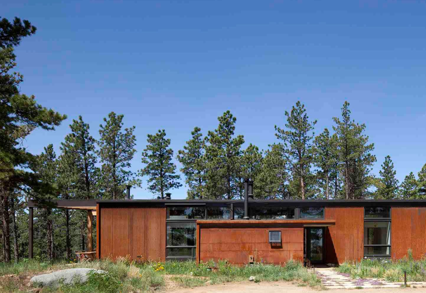 Exterior, House Building Type, Cabin Building Type, Metal Roof Material, and Flat RoofLine A linear sequence of eight, 12-foot bays extends the length of the home from rear bedrooms and an office to the open kitchen and living room space. The modest form, a reflection of the owners' desire for simplicity, required few materials: wood, concrete, and steel.  Photo by Ron Johnson.  Photo 1 of 10 in A Serene, Sustainable Home in Colorado from Serene, Sustainable Home in Colorado