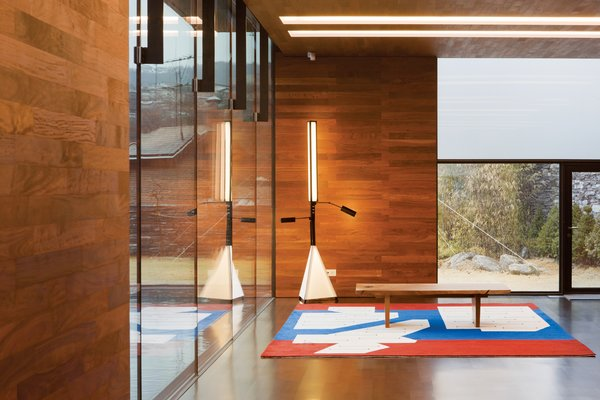 Holl designed seven rugs specifically for the home. The one in this room shows the building's interplay of structure and water; the architect also designed the light fixture next to it.  Photo 4 of 7 in Music Holl: A Copper Clad Pavilion in Seoul