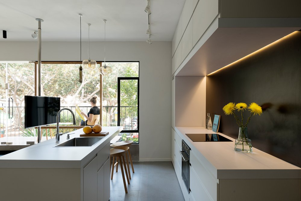 Kitchen, White Cabinet, Pendant Lighting, Engineered Quartz Counter, and Drop In Sink In the kitchen, the custom cabinets contain special compartments that hide appliances from sight. The room draws in natural light from the balcony.  Photo 9 of 11 in 10 Best Dwell Studios and Modern Apartments from A Tiny Tel Aviv Apartment Packs a Punch with No Walls