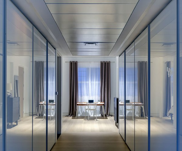 In a home where transitional spaces like corridors and closets had no natural light, the use of white glass doors for the closets help bounce light and maximize light reflections.