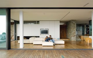 Achilleas and his girlfriend Alexia lounge on an Extrasoft sofa by Piero Lissoni for Living Divani.