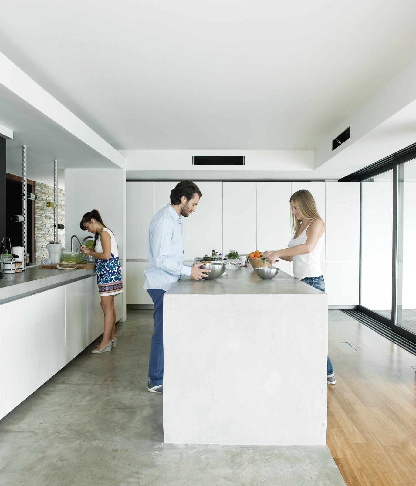 Kitchen, Concrete Counter, White Cabinet, Concrete Floor, and Light Hardwood Floor Alexia, Achilleas, and friend Fotini prepare lunch in the kitchen, outfitted with cabinets by Zeyko.  Photo 6 of 13 in An Idyllic Vacation Home in Greece