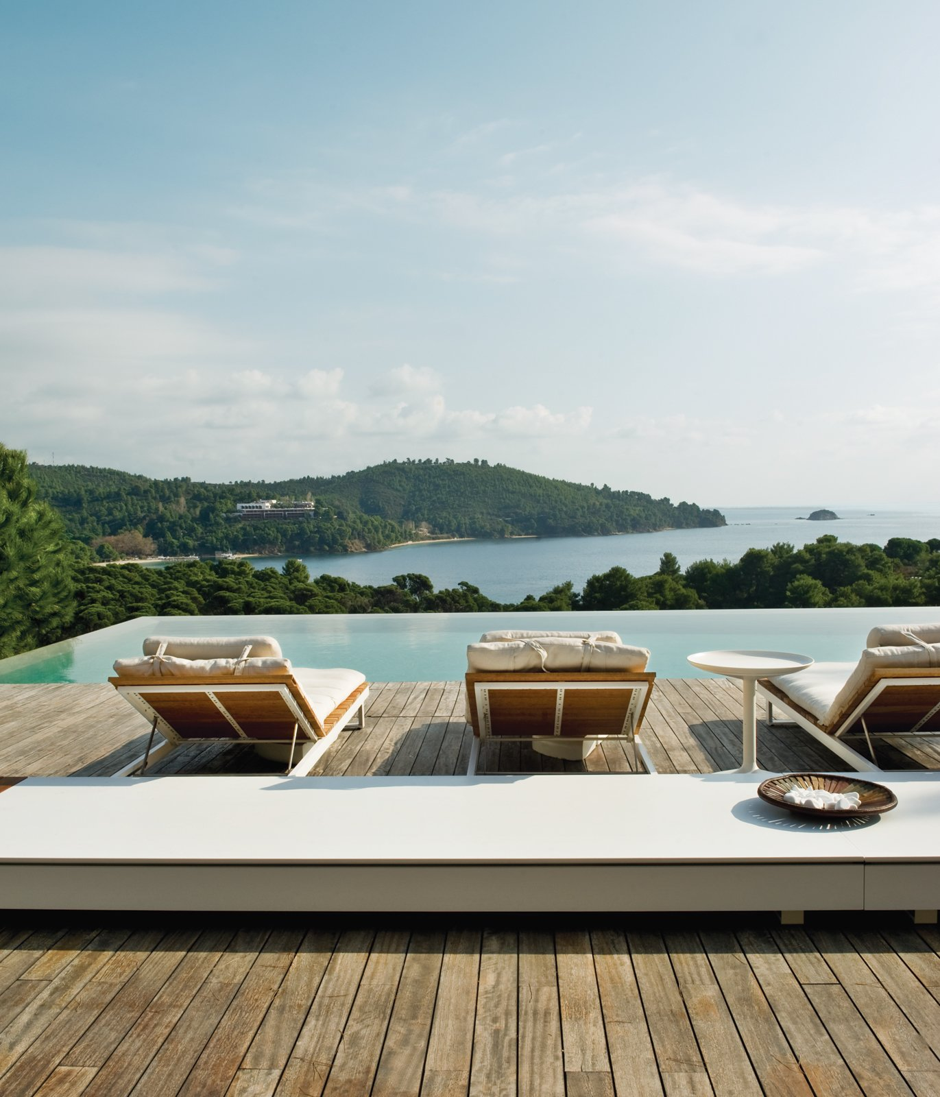 Made from white aluminum and oiled teak, the wooden sun loungers are from Viteo's Pure collection. The long low table is made of Corian by DuPont and comes from the same line of outdoor furniture.  Photo 10 of 13 in An Idyllic Vacation Home in Greece