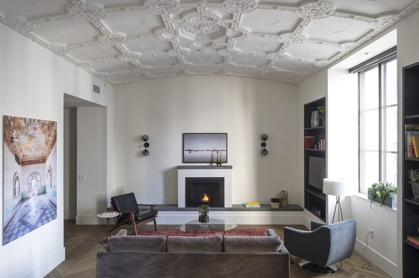 The historic vaulted ceilings were carefully restored by Morris Adjmi Architects in the renovation of the ROOST Apartment Hotel in Philadelphia. They contrast with the modern herringbone wood flooring, plush furniture selection, and clean lines of the built-in shelving and fireplace.