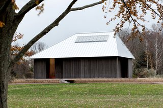 The high pitch and asymmetrical shape of this standing seam metal hip roof by architecture firm P.R.O. gives it a distinct, dramatic appearance.