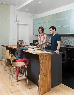 David Alan Basche, Alysia Reiner, and their six-year-old daughter, Liv, chat in the kitchen, which is defined by a reclaimed spalted maple countertop crafted from a felled 100-year-old specimen sourced by The Hudson Company. The barstools are from Blu Dot.