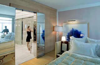 A guest room with a sliding tiled glass door leading to the luxurious bathroom.
