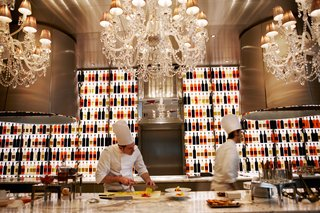 """A pair of chefs prepare dishes in the open kitchen at Raffles' one Michelin-starred restaurant, La Cuisine,  described as """"refined, generous, and spontaneous French cuisine."""""""