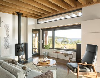 An Artist Builds a Wooden Home That Lets Nature Be the Boss - Photo 7 of 7 - The living room is furnished with a Tolomeo Mega floor lamp by Artemide, a Milo Baughman Recliner 74, a Morsø 7648 wood stove, and a Hampton rug by Capel Rugs.