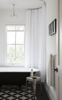 The juxtaposition of black and white is perhaps the most notable detail of the home's interiors. In the guest bathroom, black and white tiles provide visual interest.