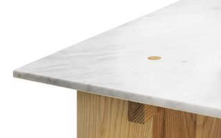 "Here's a detail of the table. It's held together by the weight of the marble slab used as a top. ""I wanted to keep the construction as clean and simple as possible so I looked into traditional joints used in basic carpentry,"" says Fjetland. ""It might sound silly, but one of the key attributes of stone is that it's rather heavy. I used the weight of the tabletop to lock the whole construction. The wooden pegs keep the stone in place and they are also prevent the solid wood flanges from getting deformed by humidity."""