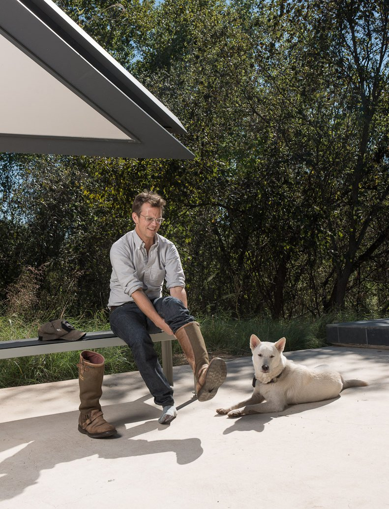 Home owner Chris Brown and his beloved dog Katsu get ready to take Dave on a tour of the Edgeland House land. Tagged: Outdoor, Trees, Concrete Patio, Porch, Deck, Grass, and Back Yard.  Photo 13 of 25 in Leap Into the Year of the Dog With These 25 Pups in the Modern World from Photographer Q&A: Dave Mead