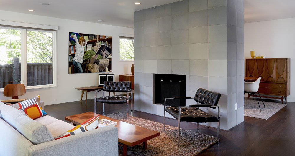 The new living room is open and bright. A hearth sheathed in concrete tile from Sadlerstone—a material that recurrs throughout the interior—is the space's focal point. Much of the vintage furniture came from Retro Inferno.  Photo 2 of 6 in Renovating a Modern House in a Historic District