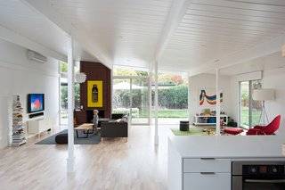 Renovated interior spaces of this 1972-1973 Eichler in California feature white on the walls, ceilings, and new structural elements—all of which let pops of color stand out, including the brick fireplace and bright artwork.