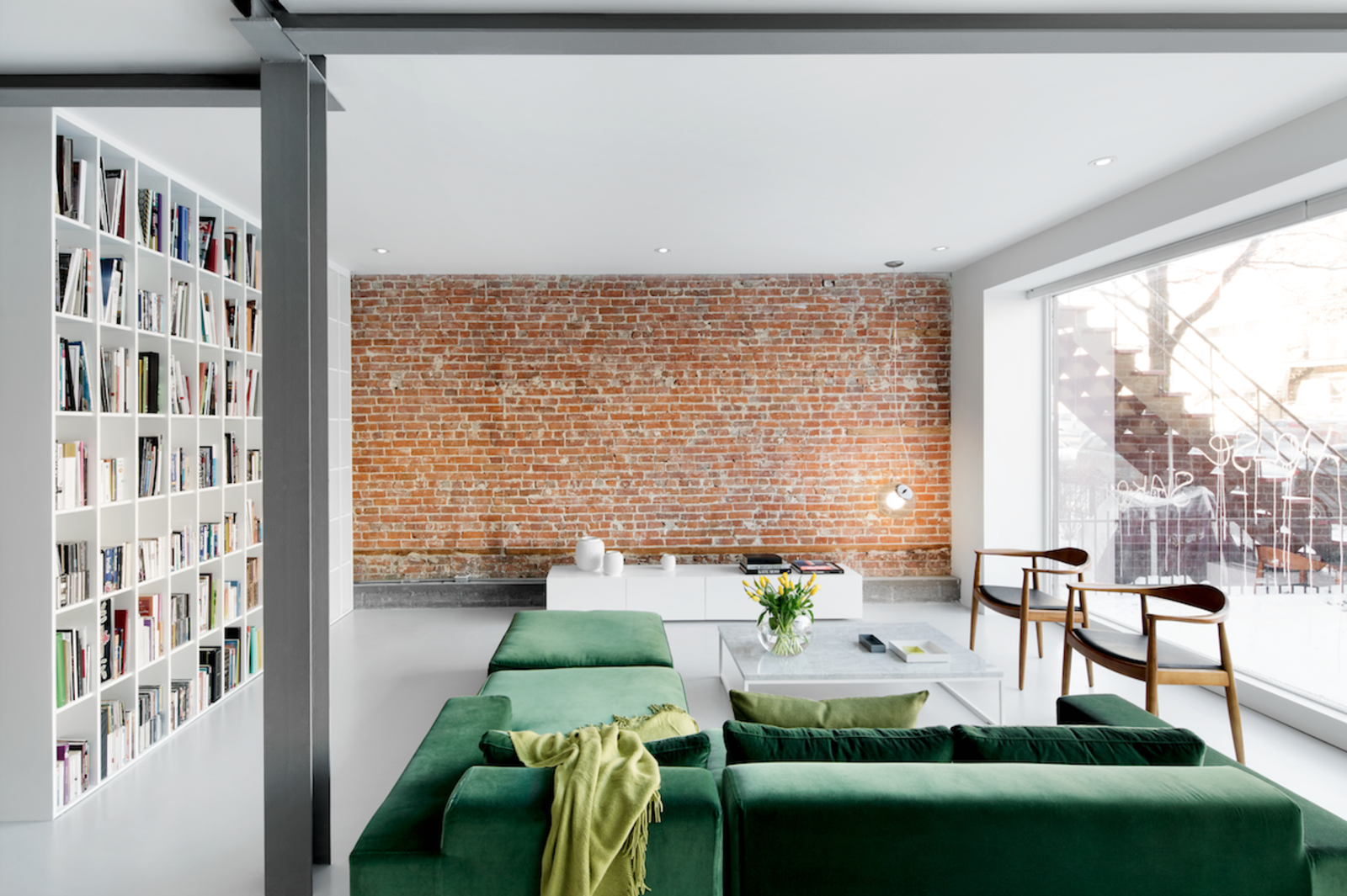 Goneau highlighted the red brick wall in the living room by leaving it bare and protecting it behind museum-quality glass. The space also features a floor-to-ceiling window that's coated on the outside with a reflective film, letting residents keep their curtains open by day without fear of being seen from the street. The green sofa is by St-Laurent Domison and the white oak chairs are by Hans Wegner. All other furniture is custom. Tagged: Living Room, Coffee Tables, Pendant Lighting, Bookcase, Chair, Console Tables, Sectional, and Concrete Floor.  Photo 1 of 10 in Revealing the Pros and Cons of Exposed Brick and How to Take Care of It from A Futuristic Apartment with a Glass-Enclosed Bedroom