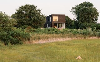Native New Yorkers, the Merola family have long held a tradition of spending summers in Rhode Island. When they learned the costs of renovating their existing cottage would significantly outweigh the benefits, they instead opted to build new. The result—a distinctively modernist box structure clad in milled slats of charred, brushed, and oiled cypress—sits nestled within the marshy landscape of Quonochontaug Pond.