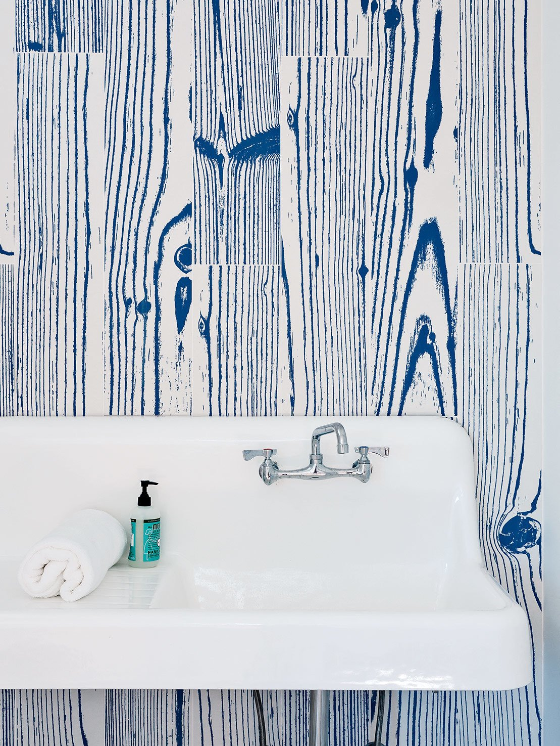 Bath Room and Wall Mount Sink White-and-blue, wood-grain–patterned UonUon tiles by 14oraitaliana line the bathroom walls in a loft above the garage.  Photo 9 of 20 in 20 Bathrooms With Transformative Tiles