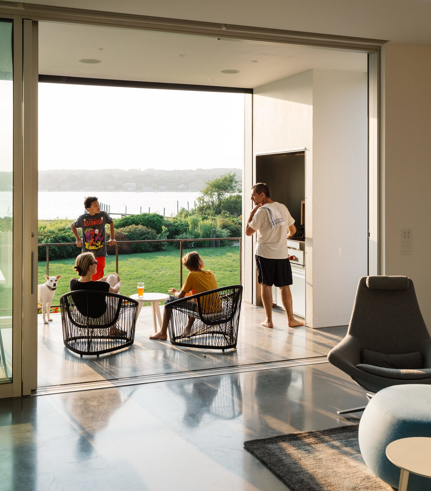 Living Room, Chair, and Coffee Tables Outside, the deck is equipped with a grill, a concrete dining table by Landscape Forms, chairs by Zanotta, and retractable insect screens from Phantom Screens—a necessity in the humid climate.  Photo 5 of 16 in An Idyllic Rhode Island Summer Cottage Is the Perfect Escape for a New York Family