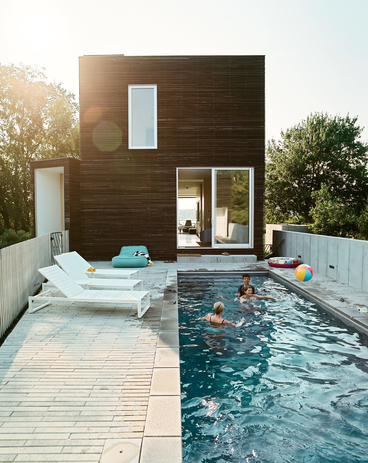 Concrete Patio, Porch, Deck, Swimming Pools, Tubs, Shower, Small Pools, Tubs, Shower, Lap Pools, Tubs, Shower, Back Yard, Exterior, House Building Type, and Wood Siding Material The east-facing pool terrace is outfitted with a series of Eos lounge chairs (and plenty of inflatable swim toys).  Photo 2 of 16 in An Idyllic Rhode Island Summer Cottage Is the Perfect Escape for a New York Family