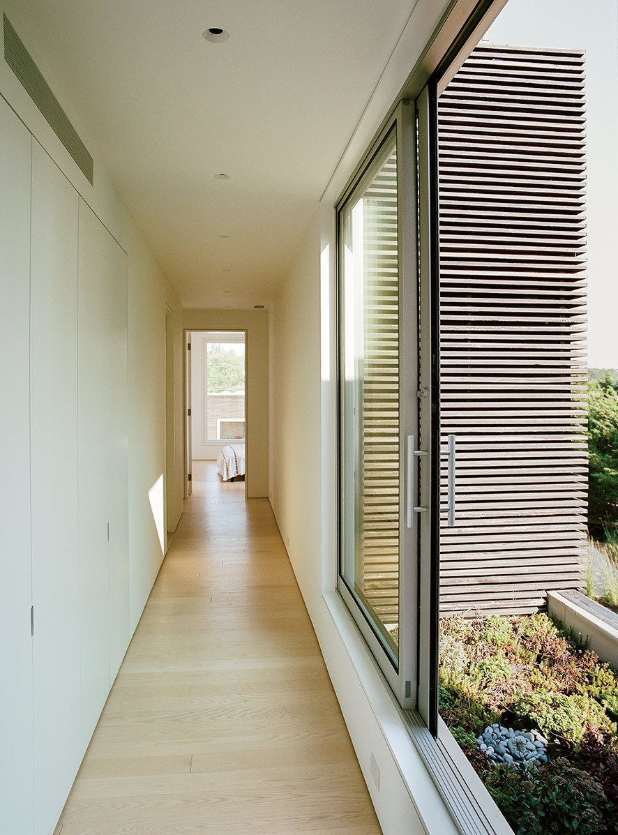 Hallway and Light Hardwood Floor The structure blends into the site's informal English-style garden, complemented with native coastal plantings by landscape designer Paula Hayes. Accessed by sliding doors, a second-floor garden is filled with a bed of low-maintenance, drought-tolerant sedum.  Photo 13 of 16 in An Idyllic Rhode Island Summer Cottage Is the Perfect Escape for a New York Family