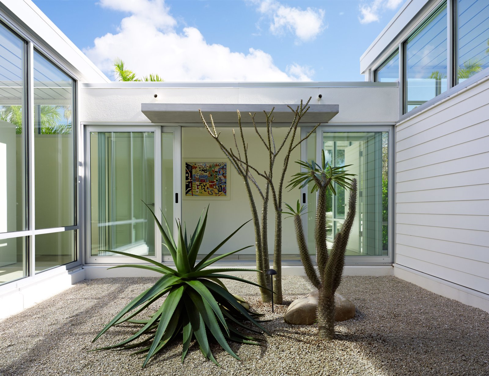 Outdoor and Garden Sliding doors from PGT Industries open onto a courtyard planted with a giant aloe and two Madagascar palms. A Nordyne HVAC system embedded in the plinth helps the house keep a low profile. The siding is by James Hardie Building Products.  Photo 9 of 13 in This Sparkling New Home Is a Perfect Remake of Classic Sarasota School Modernism