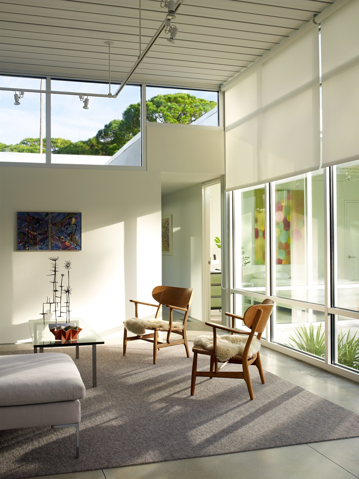 """Living Room, Sofa, Chair, Coffee Tables, Concrete Floor, and Track Lighting Float On  Clerestory windows from YKK Commercial give the illusion that the roof hovers above the house—a key factor in keeping the light, modern touch that the homeowners desired. Epstein did not design the clerestories in a single, straight line; the glass drops down where possible to allow the maximum amount of light. It took a bit of convincing to sway his clients. """"He said, 'Listen to me, stay with my concept, and you won't be sorry,'"""" Tetreault recalls. """"So I stuck with it, and I'm not sorry.""""  Photo 12 of 13 in This Sparkling New Home Is a Perfect Remake of Classic Sarasota School Modernism"""