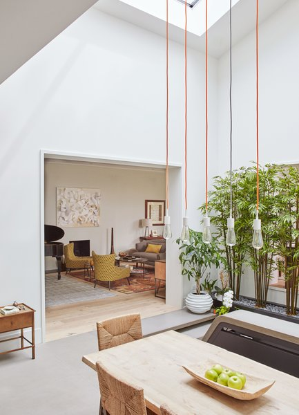 In Chicago's Buena Park, dSPACE Studio transformed a disorganized 1978 home into a bright retreat that revolves around an expanded atrium. SoCo pendant lights by Tech Lighting draw the eye up to the double-height light well.