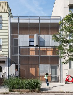 The Baumann family residence in Gowanus, Brooklyn, is all geometry up front, with a rectilinear grid of steel and cypress comprising the structure's double facade.