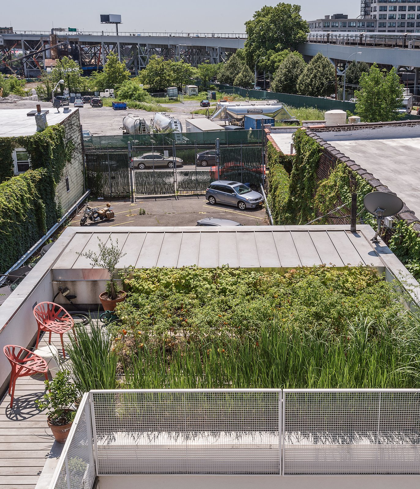 "Outdoor, Rooftop, Gardens, Grass, Wood Patio, Porch, Deck, and Decking Patio, Porch, Deck ""We have all these different destinations,"" says Sardinas, a writer who works from her home office. ""I'll be working, get stuck on a passage, and take a break to go read outside."" On the lower roof, red Vegetal chairs by Erwan and Ronan Bouroullec for Vitra provide moments for repose.  Photo 5 of 11 in 10 Modern Rooftops For Summer Relaxing and Entertaining from A Rooftop Garden Completes This Urban Pastoral Home"