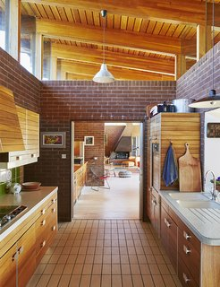 The mahogany-paneled Poggenpohl kitchen system is original to the house. The kitchen opens to the living and dining area.
