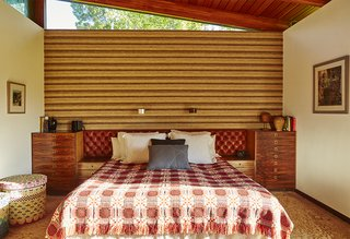 The master bedroom boasts a 1970s tufted headboard from Heals Leather and a wall covering of burlap, wool and silk by David Hicks. The bed covering is vintage, 1950s, and the Blocks linen basket was designed by Donna Wilson and made by the People of the Sun, a nonprofit based in Malawi.