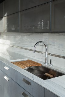 A Kallista sink and faucet abuts the back wall.