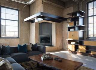 The modern fireplace is located at the original chimney stack of the building. Robb Studio created a sculptural fireplace using exposed concrete, steel, and shou sugi ban wood for the hearth seat.