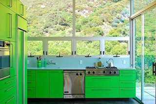 Taking cues from the outlying rolling landscape of this Malibu home, architect Bruce Bolander selected a bright green hue for the cabinets and refrigerator of this kitchen. The connection to nature is evident, thanks to the grand views through the windows above the sink and stovetop area.