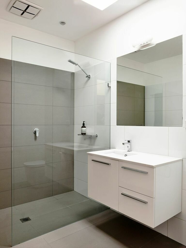 "Bath Room, Wall Mount Sink, and Full Shower ""Keeping the kitchen and bathrooms simple saved money for the important things,"" Harkness explains. They went with a soothing color palette and hardware from Reece.  Photo 5 of 8 in A Breezy Modern Beach House Sits Among the Trees in Australia"