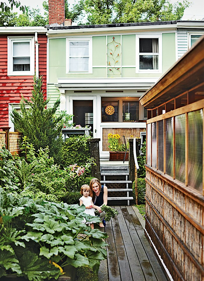 Outdoor and Garden Lyle Bradley spent years of weekends and evenings resurrecting an East Boston structure using his carpentry skills, repurposed materials, and clever space-saving interventions. The revitalized 800-square-foot residence joins a rejuvenated backyard, where Bradley's wife, Kara Lashley, and their daughter, Lily, pose next to Bradley's new freestanding workshop.  Photo 3 of 8 in 8 Great Examples of Outdoor Design from Run-Down Row House in Boston Becomes a Quiet Urban Escape with Two Green Roofs